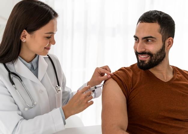 Médico vacinando um homem bonito