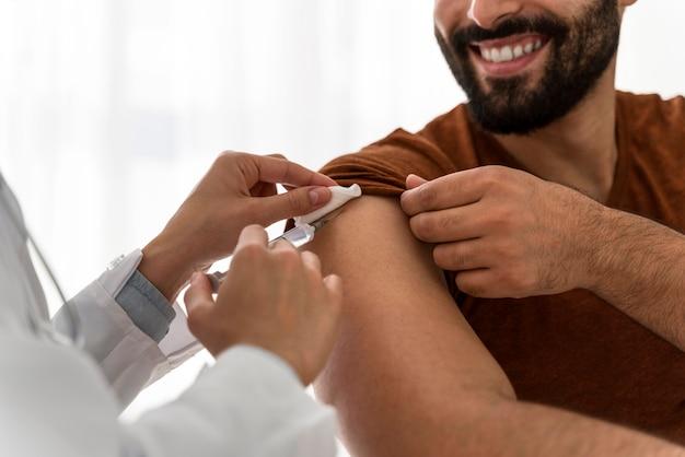 Médico vacinando um homem sorridente