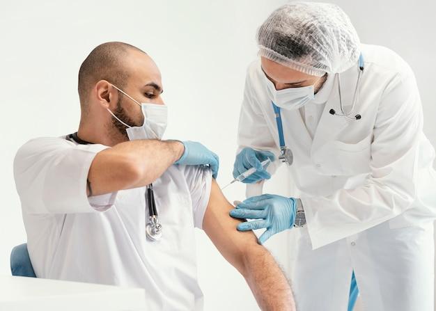 Médico vacinando um paciente na clínica