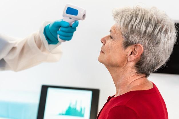 Médico verifica a temperatura corporal de uma mulher idosa usando termômetro infravermelho para testa