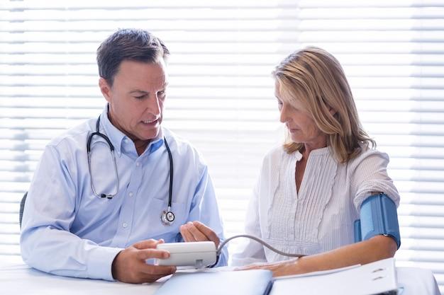 Médico, verificação de pressão arterial de um paciente na clínica
