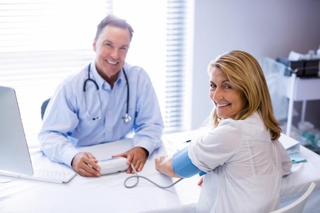 Médico, verificação de pressão arterial de um paciente