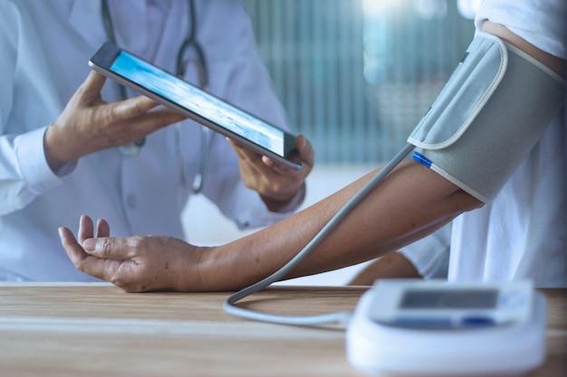 Médico, verificação de pressão arterial