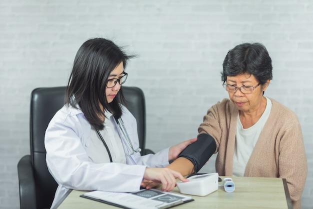 Médico, verificação de pressão mulher velha no fundo cinza