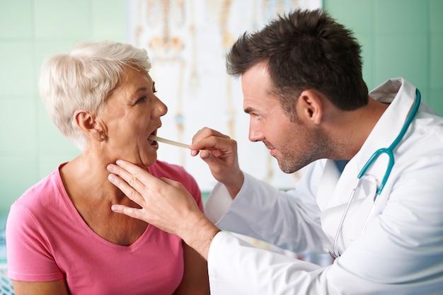 Médico verificando a garganta da mulher sênior