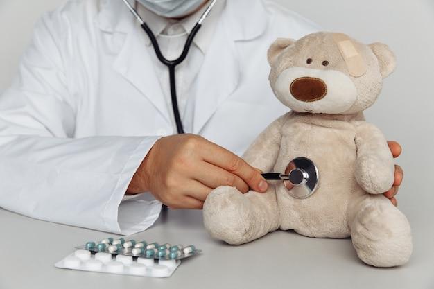 Médico, verificando o batimento cardíaco de um ursinho de pelúcia no hospital. conceito de pediatra.