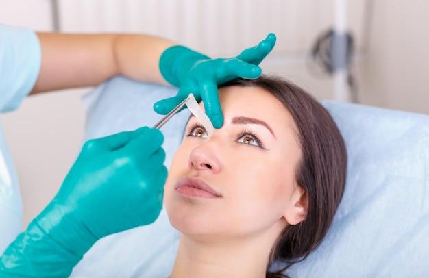 Médico, verificando o rosto da mulher, a pálpebra antes da cirurgia plástica, blefaroplastia.