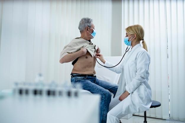 Médico, verificando o sistema respiratório e os pulmões do velho com estetoscópio no escritório do hospital durante a pandemia do vírus corona.