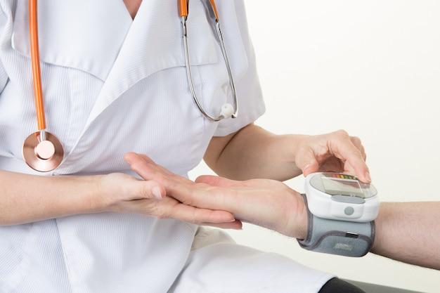 Médico, verificar a pressão arterial do paciente no hospital em monitor digital