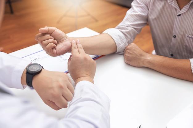 Médico verificar a pressão sangüínea do paciente no escritório.