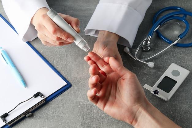 Médico, verificar o nível de açúcar no sangue em paciente diabetes na mesa cinza