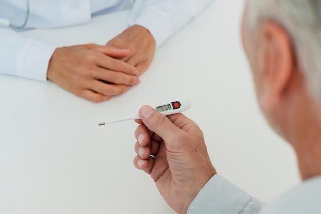 Médico verificar termômetro