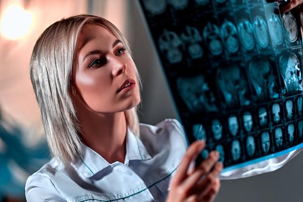 Médico vestido com um uniforme branco examina uma ressonância magnética do cérebro