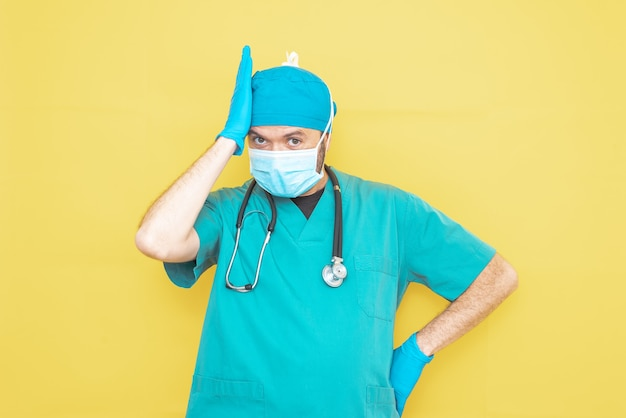Médico vestido de cirurgião de verde com estetoscópio e máscara em um fundo amarelo com uma expressão preocupada.