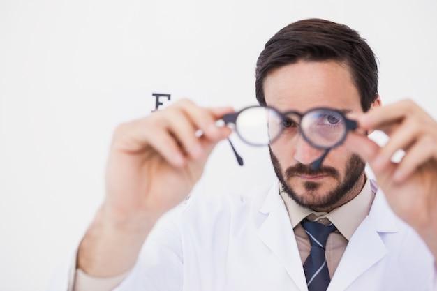 Médico vestindo bata de laboratório olhando através de óculos