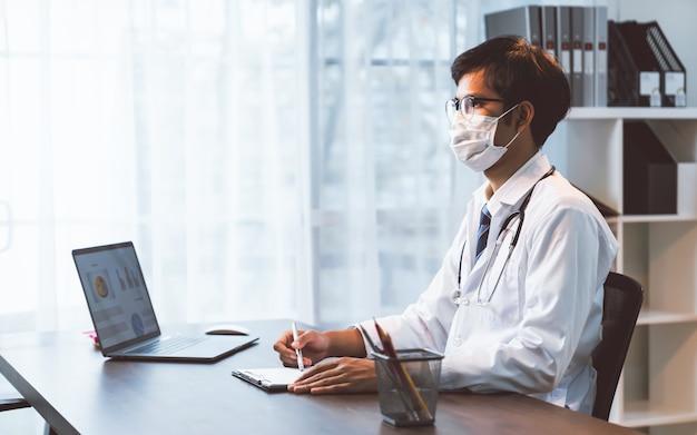 Médico vestindo máscara sentado à mesa