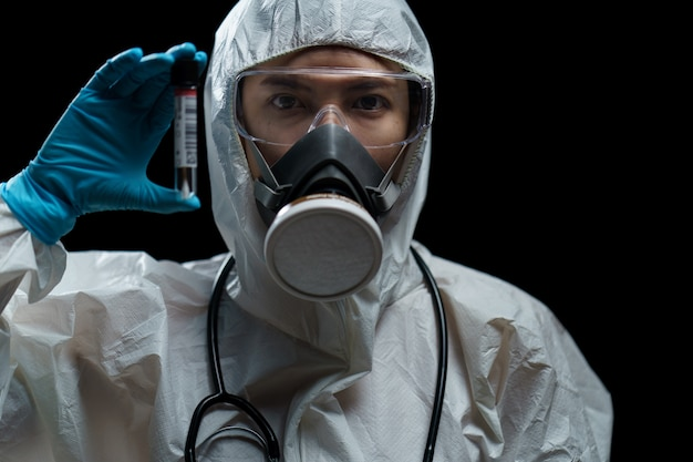 Médico vestindo ternos de hazmat com kit de coleta de cotonete no laboratório