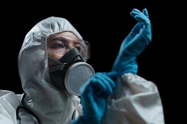 Médico, vestindo trajes perigosos, máscara respiratória, óculos de segurança e luvas médicas em laboratório