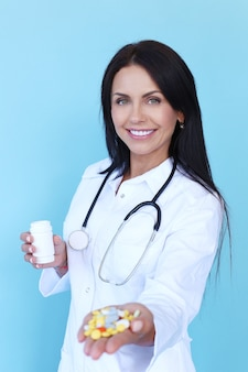 Médico vestindo túnica branca e estetoscópio segurando comprimidos