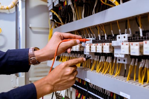 Medições de eletricista com corrente de teste de multímetro elétrica no painel de controle.