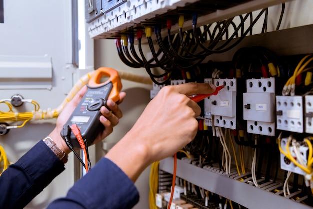 Medições do eletricista com multímetro testando corrente elétrica no painel de controle.