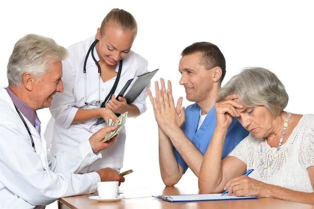Médicos à mesa em fundo branco isentando raio-x