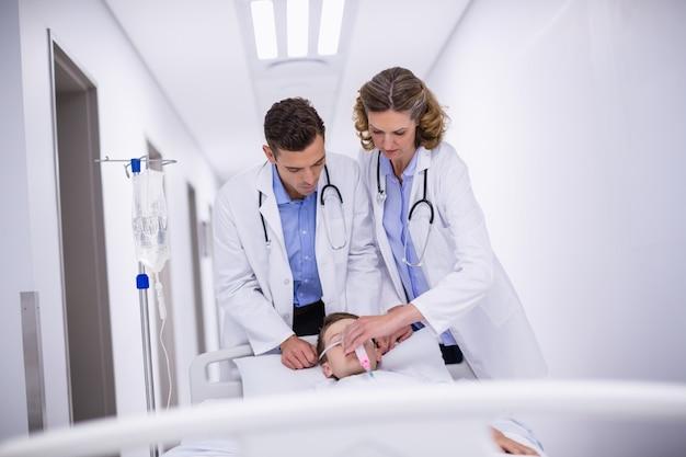 Médicos ajustando máscara de oxigênio enquanto apressam o paciente na sala de emergência