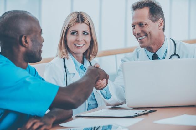 Médicos apertando as mãos. dois médicos alegres apertando as mãos enquanto estão sentados com a médica