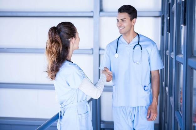 Médicos, apertando as mãos no corredor do hospital