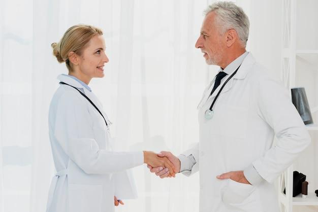 Médicos, apertando as mãos vista lateral