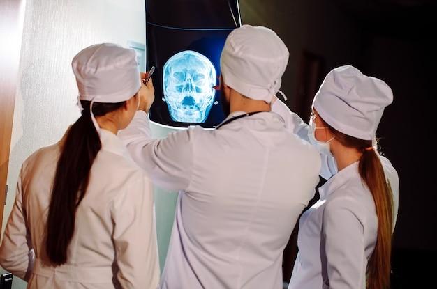 Médicos assistindo raio-x do paciente.
