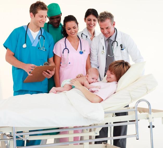 Médicos atendendo a um paciente e um bebê recém-nascido