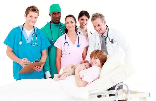 Médicos atendendo a uma mãe e seu bebê recém nascido