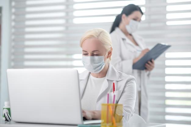 Médicos, colegas. mulher loira, trabalhando em um laptop, morena com uma pasta perto da janela, em máscaras protetoras e jalecos brancos.