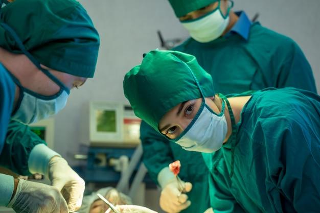 Médicos com a equipe de cirurgia operando em uma sala cirúrgica no hospital.