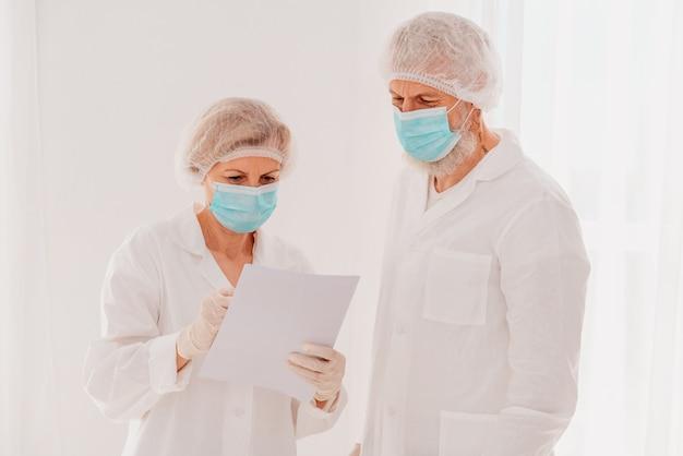 Médicos com máscara facial trabalham juntos no hospital