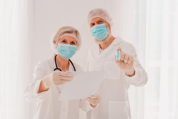 Médicos com máscara mostram a vacina contra o vírus cobiçado