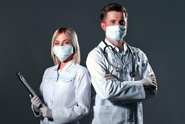Médicos com máscaras de proteção e luvas em um fundo cinza escuro