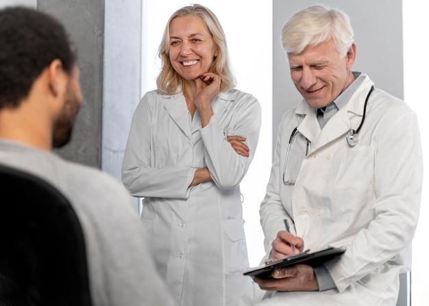 Médicos conversando com um jovem paciente