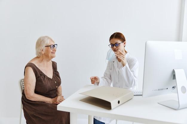 Médicos conversando com uma mulher idosa no consultório médico