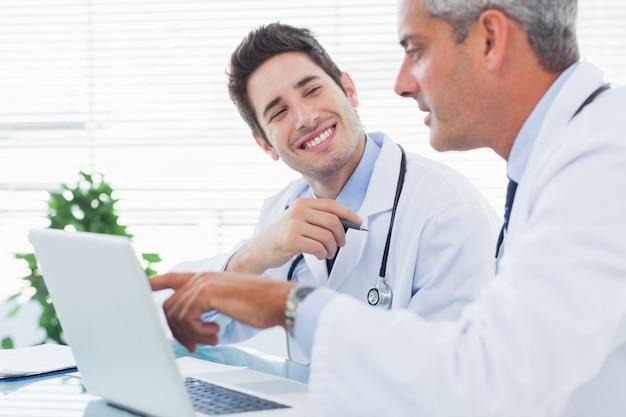 Médicos conversando sobre algo em seu laptop
