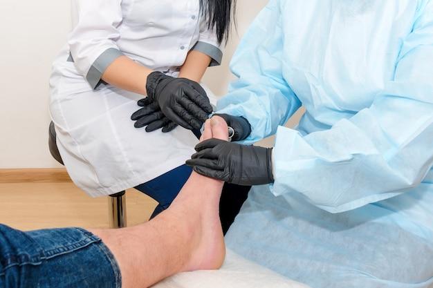 Médicos da podologia tratam o paciente em clínica moderna
