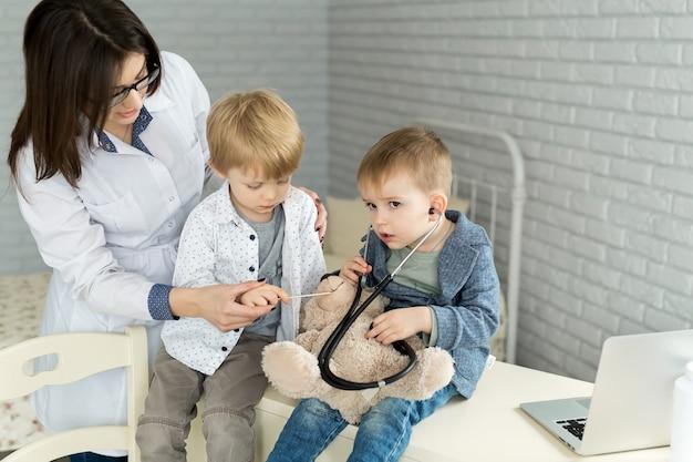 Médicos de crianças brincam com um paciente de brinquedo