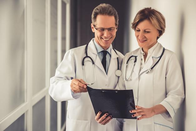 Médicos de jaleco branco discutem documentos.