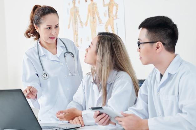 Médicos discutindo dados na tela do laptop