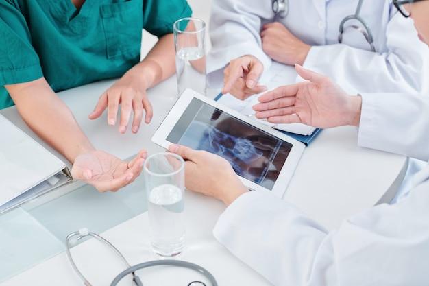 Médicos discutindo raio-x de mandíbula
