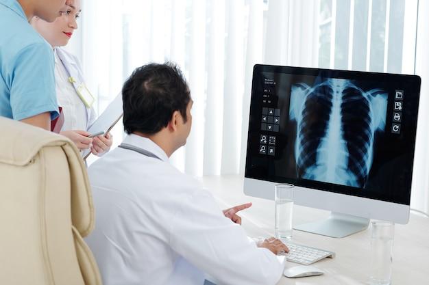 Médicos discutindo raio-x de pulmão