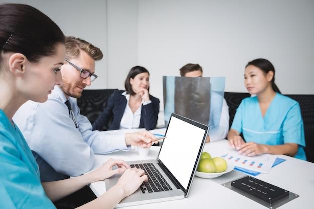 Médicos discutindo sobre laptop em reunião