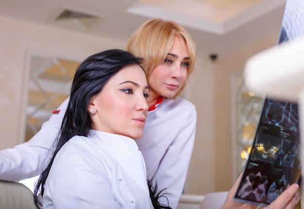 Médicos do sexo feminino olhando um raio-x da tomografia