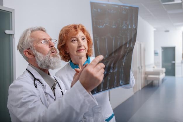 Médicos do sexo masculino e feminino idosos examinando a ressonância magnética juntos